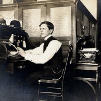 Büro,-Junger-Mann-mit-Zigarette-am-Sekretär